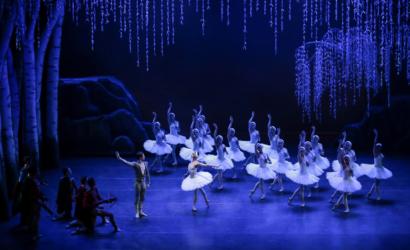 Sob luz azulada, conjunto de bailarinas com tutus brancos estão no lado direito, com um dos braços erguidos. Ao centro, um cisne bloqueia o acesso do príncipe que está com uma besta na mão.