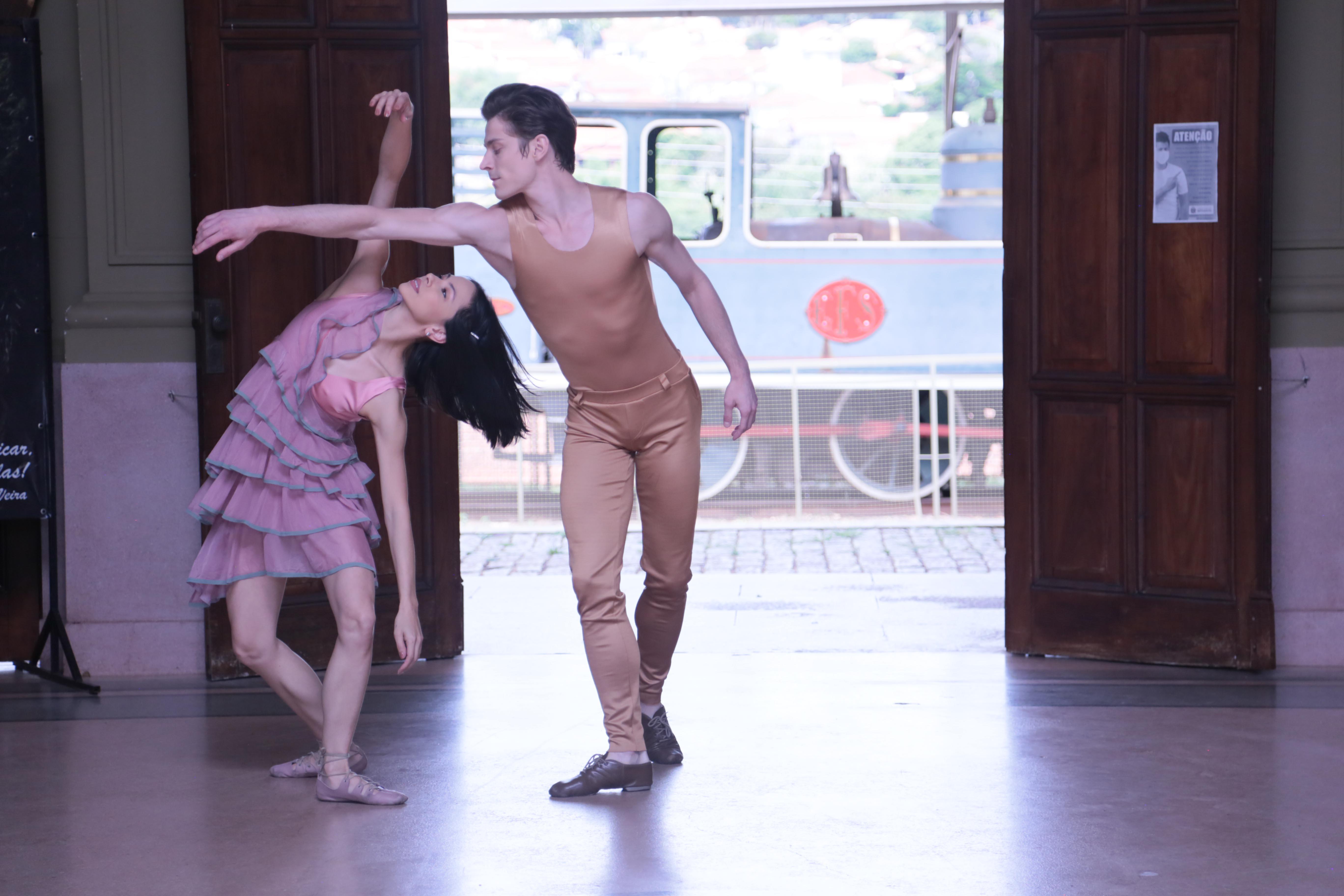 Diante de uma porta aberta com imagem de um trem azul ao fundo, casal de bailarinos dança, ela de vestido lilás de babados, ele com calça e camiseta nude