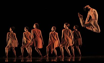 Sob fundo preto, seis bailarinas estão de costas, com vestidos em tons de laranja com comprimento no meio das coxas, os joelhos flexionados e o rosto de perfil para o público. Em primeiro plano, à direita, um bailarino de torso nu e calça bege salta arqueando o tronco e as pernas para trás, como se quisesse encostar a cabeça nos pés